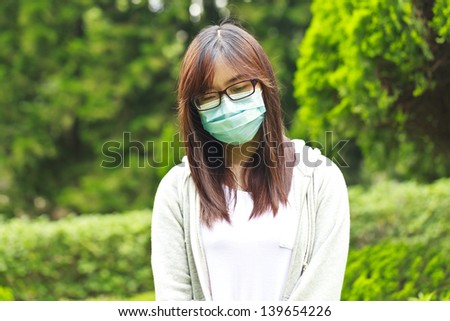 Woman wearing mask in park - stock photo