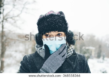 Woman wearing medical face mask in crowded city.  Female wearing face mask, protection from virus infection in winter time, feeling bad with headache - stock photo