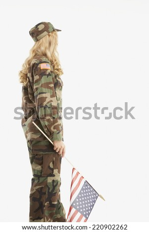 Woman wearing military uniform and holding American flag - stock photo