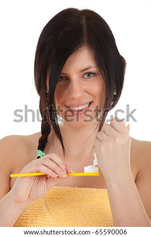 woman wearing only a bright yellow towel prepares to brush her teeth - smiling (oral hygiene or health)