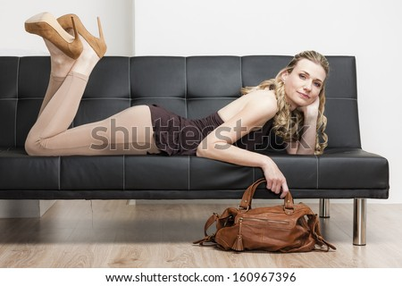 woman wearing pumps with a handbag lying on sofa
