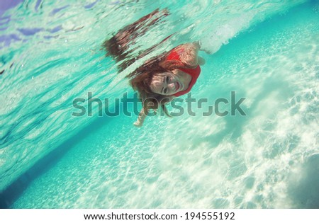 Woman wearing red and swimming in the ocean