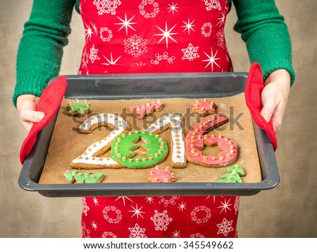 Woman wearing red apron holding home-made gingerbread cookies in shape of 2016 New Year digits on baking tray - stock photo