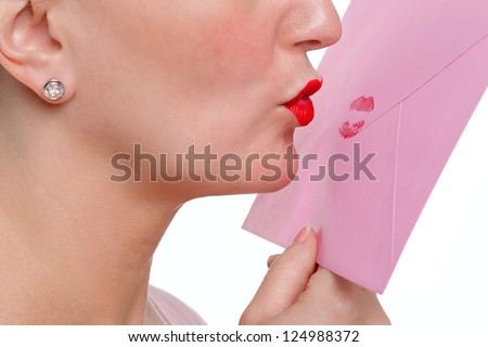 Woman wearing red lipstick kissing an envelope - Sealed With A Loving Kiss or SWALK for short. - stock photo