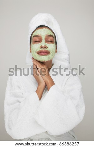 Woman wearing robe with beauty mask on face - stock photo