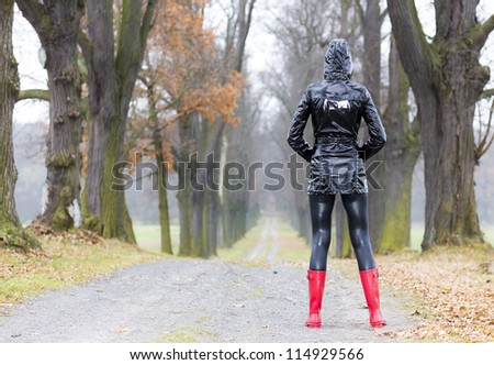 woman wearing rubber boots in autumnal alley - stock photo