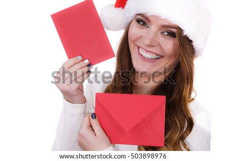 Woman wearing santa claus hat holding red envelope reading children letter or wish list. Positive face expression. Christmas time. Studio shot isolated on white