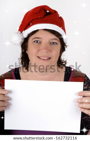 Woman wearing Santa's hat and holding a sign with copy space - stock photo