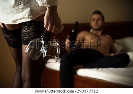 Woman wearing sexy stockings holding glass of wine - stock photo