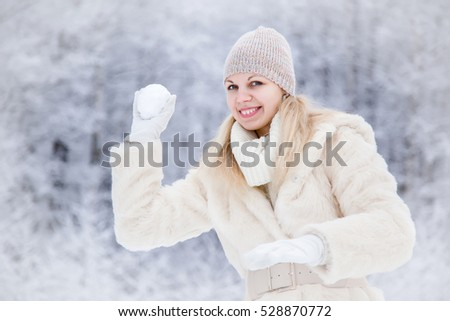 Woman wearing soft fur coat and enjoying a beautiful winter day and playing with snowball in the park.