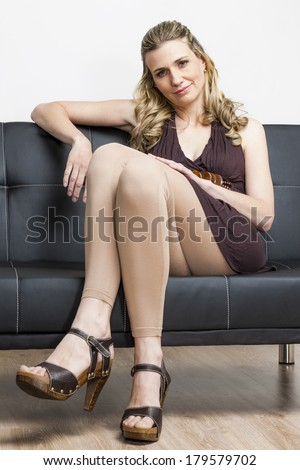 woman wearing summer shoes sitting on sofa - stock photo