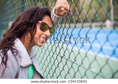 Woman wearing sunglasses over tennis court background