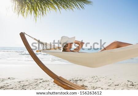 Woman wearing sunhat and bikini relaxing on hammock at the beach - stock photo