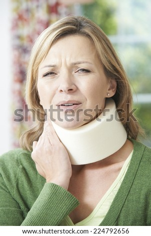 Woman Wearing Surgical Collar In Pain - stock photo