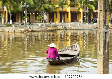 Woman wearing the conical hat and rowing her little boat on the river at Hoi An - stock photo