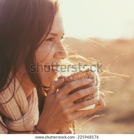 Woman wearing warm knit clothes drinking cup of hot tea or coffee outdoors in sunlight, instagram toned, square composition - stock photo