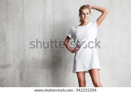 Woman wearing white blank t-shirt  standing on the background of a cement wall - stock photo