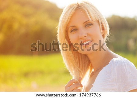 Woman wearing white dress, in wheat field during summer day.  - stock photo