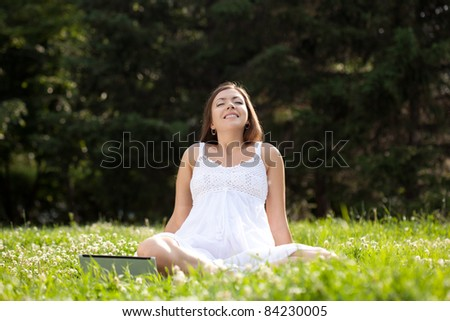 woman wearing white dress sitting on grass in park with netbook - stock photo