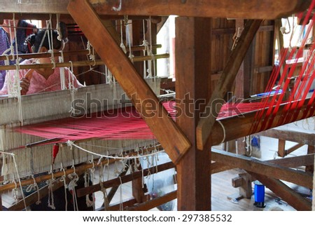 Woman weaving bright red silk fabric on a wooden loom,  Inle Lake,  Myanmar (Burma)