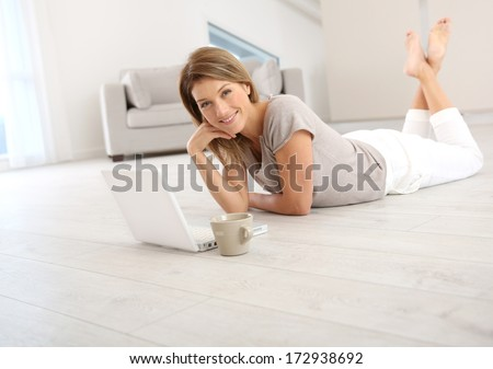 Woman websurfing on the net with laptop - stock photo