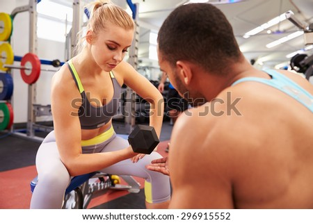 Woman weight training at a gym getting advice from a trainer - stock photo