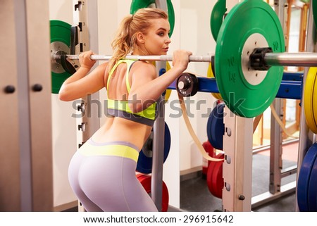 Woman weightlifting barbells at a squat rack in a gym - stock photo