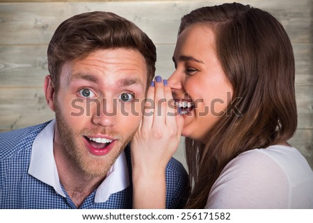 woman whispering secret into friends ear against bleached wooden planks background - stock photo