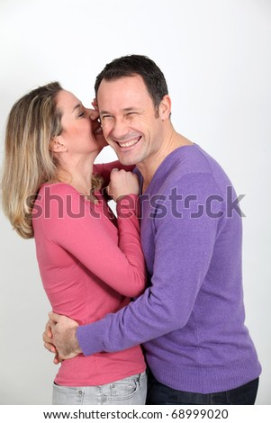 Woman whispering to her boyfriend's ear - stock photo