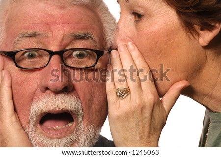 Woman whispers a scary secret into husband's ear - stock photo