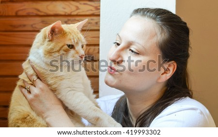 Woman who adores her ginger cat  and holds her in her arms - stock photo