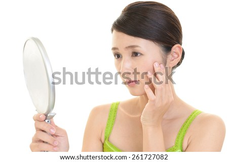 Woman who is looking at herself in a mirror - stock photo