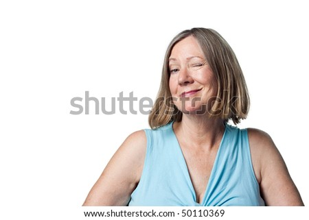 Woman winks at the camera in a playful flirtatious, knowing way - stock photo
