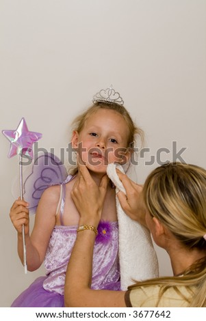 Woman wipes off lips of little girl - stock photo