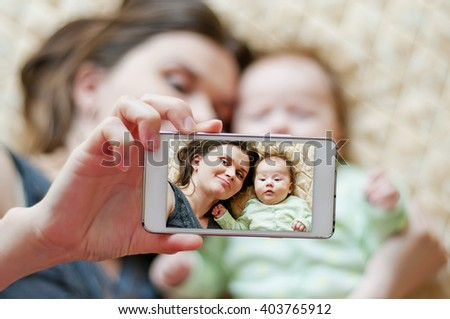 Woman with a baby doing a selfie lying on bed