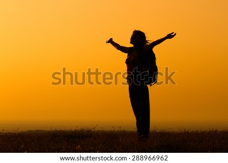 Woman with a backpack enjoys in sunset.Woman hiker greeting the sunset - stock photo