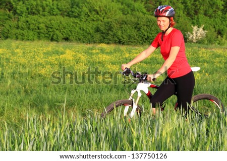 Woman with a bike on the green field outdoor - stock photo