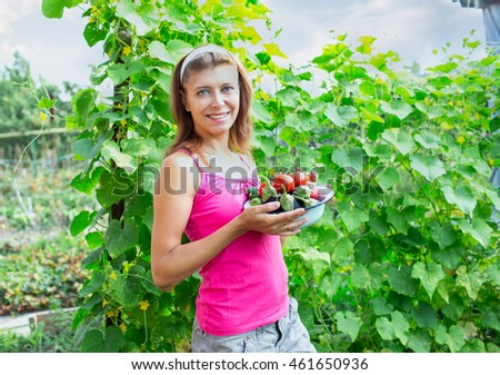 Woman with a bowl of vegetables in the garden