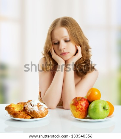 woman with a buns and fruits choose between healthy and unhealthy food - stock photo