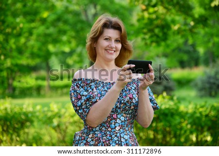 woman with a cell phone in nature in the summer - stock photo