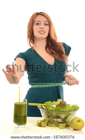 Woman with a centimeter on her waist thinking on dieting while eating organic healthy salad,fruits and smoothie for a perfect body. Green food for a healthy life