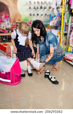 Woman with a child to buy clothes in shop - stock photo