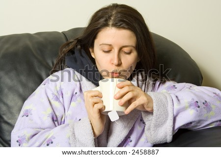 woman with a cold blowing hot tea - stock photo
