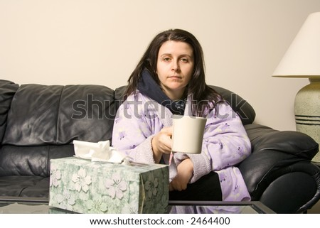 woman with a cold holding a cup with a hot tea - stock photo