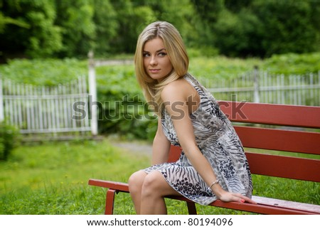 Woman with a dress sitting on a red bench in the garden a summer day