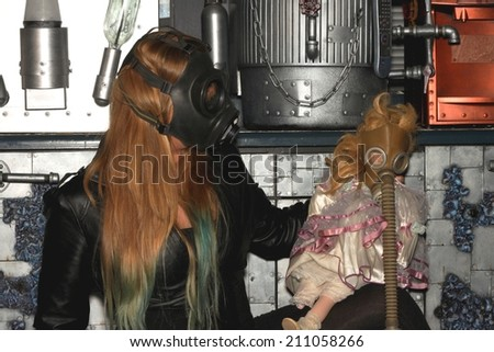 Woman with a gasmask and a puppet in front of a a wall. - stock photo