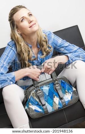 woman with a handbag sitting on sofa - stock photo