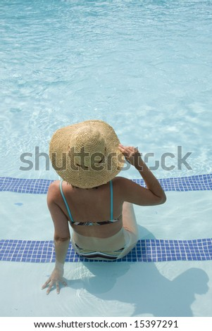 woman with a hat relaxing in the pool - stock photo