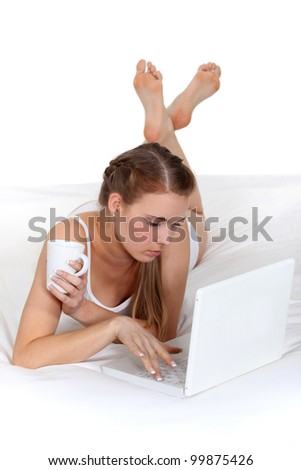 Woman with a laptop and coffee in bed - stock photo