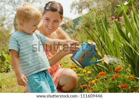 woman with a little son watering flowers/Little boy with his mother watering from a watering can. Summer, sunny day - stock photo